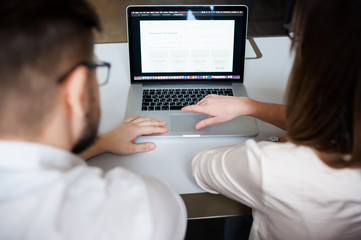 Two young coworkers dressed casual using laptop in white interior