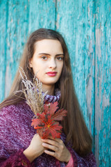 Portrait of a pretty young teenage girl 13-16 years old. Young woman with autumn flowers closeup.