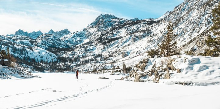 Girl walking across frozen lake with mountains in background
