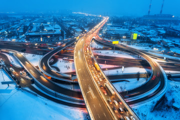 Aerial view of the road in modern city at night in fog. Top view of traffic in highway. Winter cityscape with elevated road, cars, buildings, illumination.  Interchange overpass in Europe. Expressway