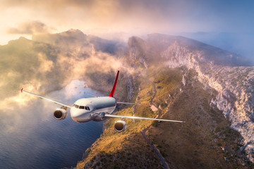 Airplane is flying over mountains and low clouds at sunset in summer. Landscape with passenger airplane, sky in clouds, rocks, sea, sunlight. Business travel. Commercial plane. Aerial view of aircraft