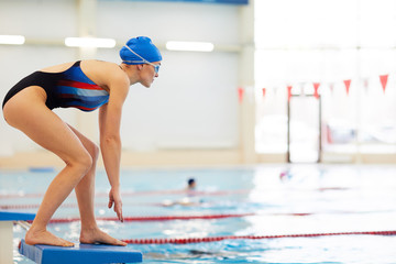 Side view portrait of female swimmer on start position in swimming pool, copy space