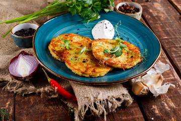 Close-up view of potato pancakes. Potato cake on a blue plate above a wooden table, with fresh parsley and sour cream.