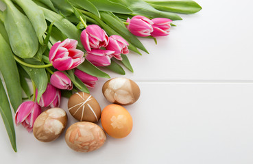 Easter background with bouquet of pink tulips and colorful eggs .