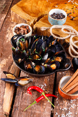 Boiled mussels in copper dish for cooking on wooden background, near rope and products for cooking