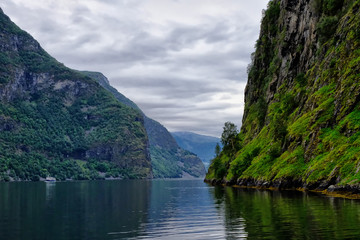 Holy grail illustrated from Sognefjord or Sognefjorden created from mountain range with blue sky and reflection in clear water and having a wooden dock point out in a river in Flåm