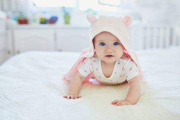baby girl relaxing in bedroom in pink clothes or towel with ears