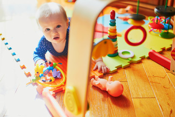 Baby girl playing with toys on the floor