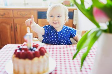 Happy baby girl in blue dress celebrating her first birthday