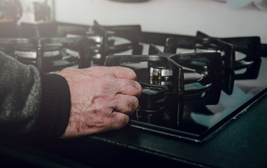 View of a man unscrewing a gas cock. Using a gas oven to prepare dishes. The man fires the gas to start cooking.