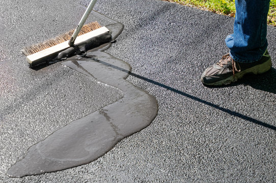 Spreading asphalt resealer onto driveway for maintenance