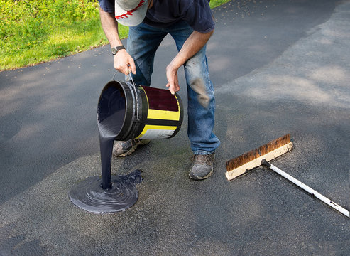 Pouring asphalt onto driveway for resealing