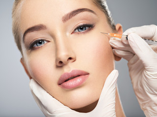 Woman getting cosmetic injection of botox in cheek