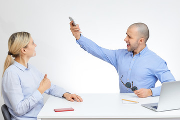 Happy brutal boss in a blue shirt in stylish sunglasses takes a photo of his blonde caucasian handsome colleague sits by the desk in the office with the white background.