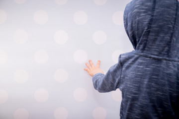 Rear view of a boy with a hood. The boy stands with his face veiled in the direction of the wall. The concept of loneliness, fun.