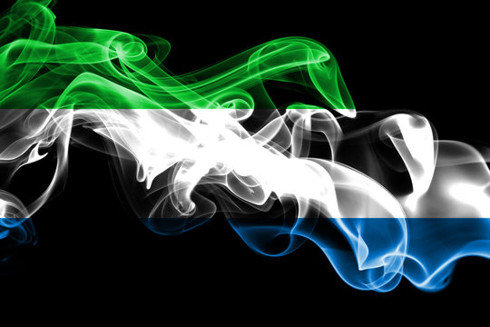 National flag of Sierra Leone made from colored smoke isolated on black background. Abstract silky wave background.