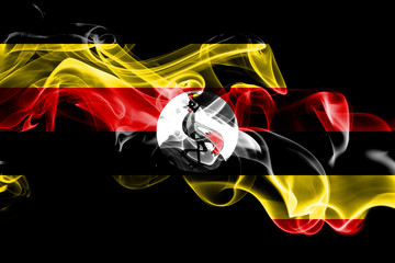 National flag of Uganda made from colored smoke isolated on black background. Abstract silky wave background. Wall mural