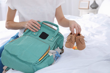 Woman packing baby accessories into maternity backpack on bed, closeup