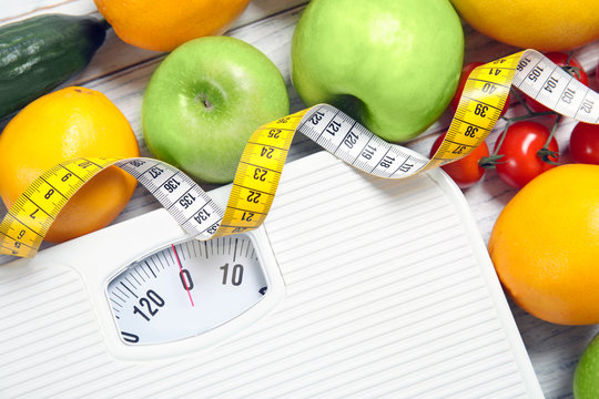 Scales, measuring tape and healthy food on wooden background, closeup. Weight loss