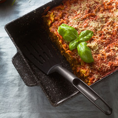 vegan lasagna with lentils and green peas in a baking sheet on a table with a blue linen tablecloth. healthy Italian cuisine for the whole family, party or restaurant and red wine in glasses