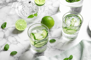 Glasses with fresh cucumber water on table