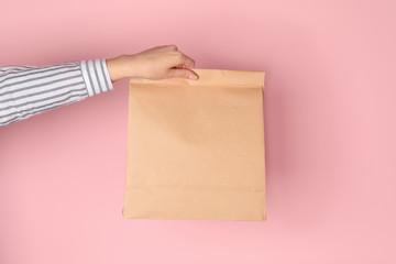 Woman holding paper bag on color background. Mockup for design Fototapete
