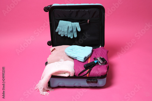 bc5046ce91e Open suitcase with warm clothes and action camera on color background.  Winter vacation
