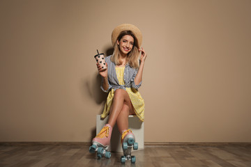 Young woman with retro roller skates and cup of drink against color wall