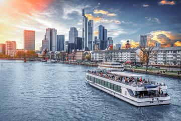 Evening over Main river with touristic cruise boat, illuminated sunset and Frankfurt skyline of modern architecture at sunset, Germany, Europe