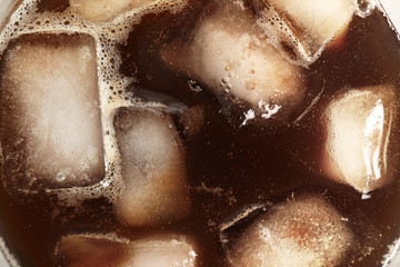 Coffee drink with ice cubes in glass, top view
