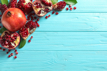 Composition with ripe pomegranates and space for text on wooden background, flat lay