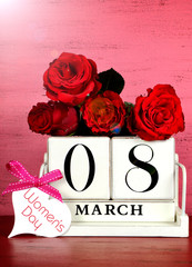 International Women's Day white vintage wood block calendar date for March 8, with roses on pink and red vintage wood with lens flare filters.