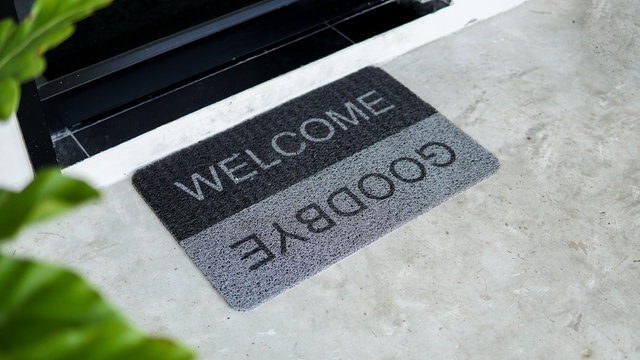Front door with doormat plants with welcome,goodbye written on it