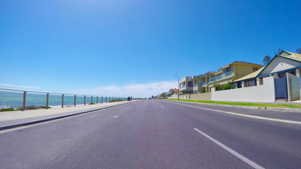 Vehicle POV, driving along The Esplanade, Henley Beach, South Australia with views of ocean and beach, and homes overlooking the sea.