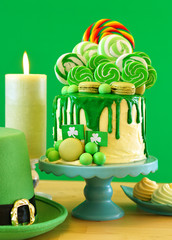 St Patrick's Day party table with lollipop candyland drip cake on green background.