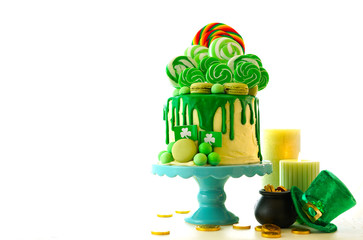 St Patrick's Day party table with lollipop candyland drip cake on white background with copy space.
