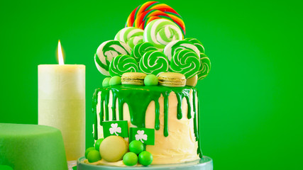 St Patrick's Day party table with lollipop candyland drip cake on green background, close up.
