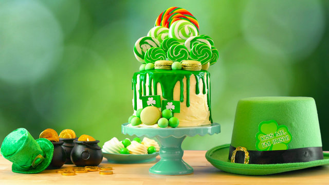 St Patrick's Day party table with lollipop candyland drip cake against bokeh garden background.