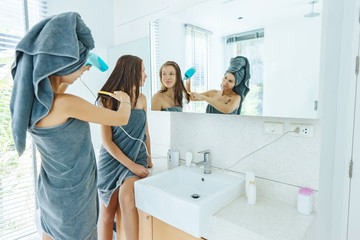 Mom brushing hair to her daughter in hotel bathroom
