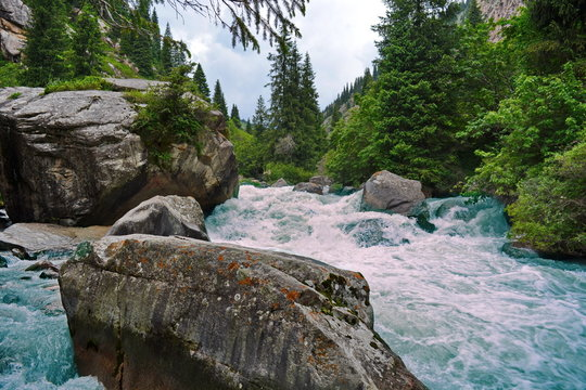 turbulent water flow in the mountain river between rocks and large boulders after hard rain with blue water and white foam