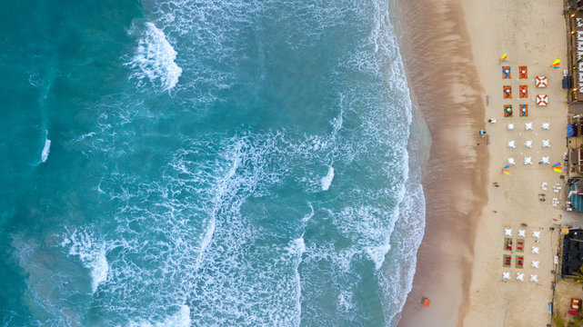 Aerial : Overhead  of people enjoying the summer at sand  beach resort line ,waves breaking against the coast