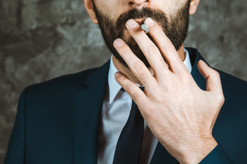 Businessman smoking a cigarette on dark background