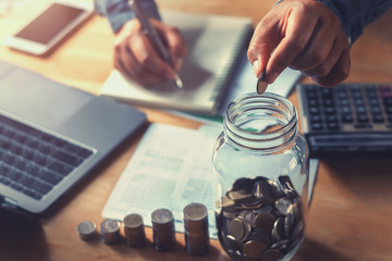 accountant saving money hand holding coins putting in jug glass. concept finance and accounting