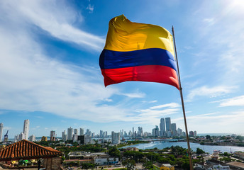 The Colombian flag waving in the wind. Blue sky with white clouds in the background. The city of Cartagena is in the far back. Shot in Cartagena, Colombia, USA.