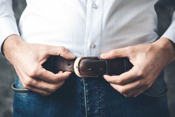 man hand on belt on dark background