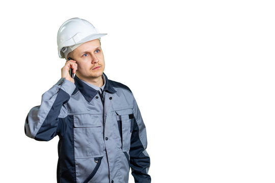 An engineer in a white helmet talking on the phone on a white background. He listens to the boss or new tasks for the repair of construction. isolated