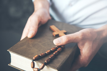 man hand holding  cross with Bible