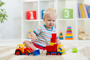 Nursery kid playing toy cars at home or kindergarten