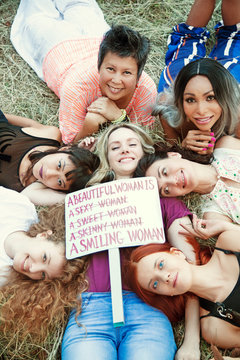 """Group of women in nature with a poster """"""""A beautiful woman is a smiling woman""""  International Womens Day concept."""