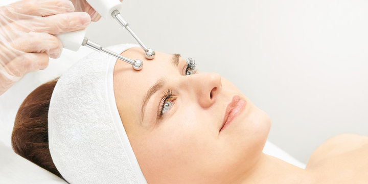 Microcurrent esthetics procedure. Beauty girl face. Cosmetology machine. Doctor hands. Two micro balls. Wrinkle reduction
